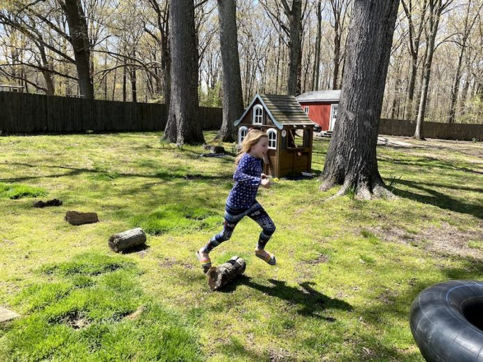 child jumping over logs
