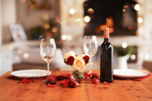 Romantic dinner table setting with wine and flowers