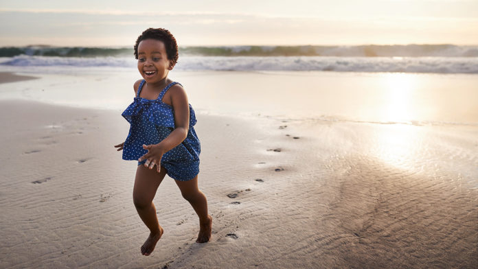 Shot of an adorable little girl having fun on the beach at sunset