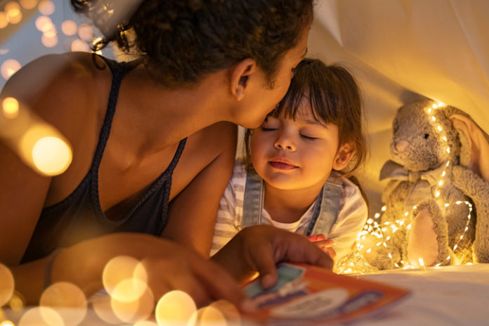 African american mother kissing her daughter on forehead while lying on bed in illuminated tent. Close up of mom kissing little cute girl with closed eyes holding story book in tent. Mother putting daughter to sleep in cozy hut after reading a fairy tale.