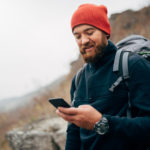 Young bearded man smiling and sending messages for his family from his cellphone, during hiking in mountains. Traveler bearded man in red hat using mobile phone application