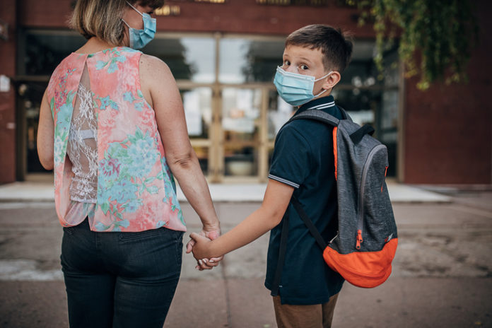Mother and her son schoolboy going home from school together, they are wearing surgical mask do to coronavirus and holding hands.