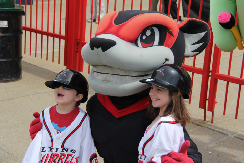 Flying squirrel mascot posing with kids