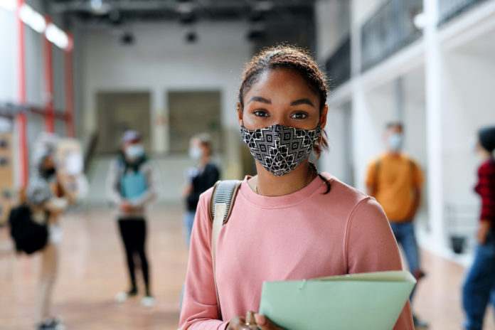 Student at school with mask on holding books